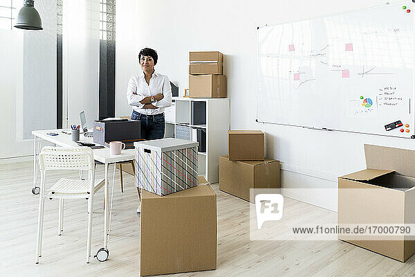 Portrait of businesswoman standing in office filled with cardboard boxes
