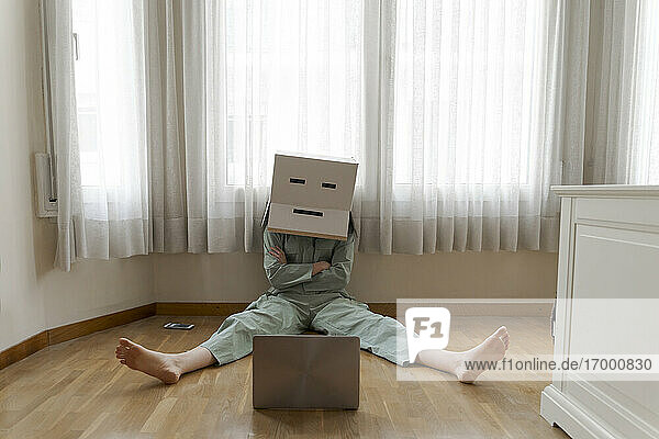 Woman wearing a cardbox on head with bored smiley sitting on floor and looking at laptop