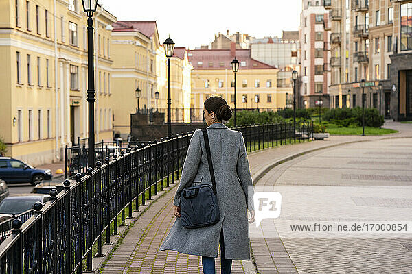 Female entrepreneur walking on footpath in city during autumn