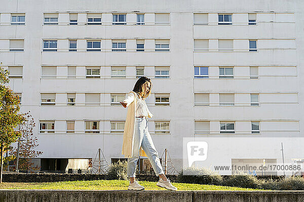 Female entrepreneur with arms outstretched walking in garden by building