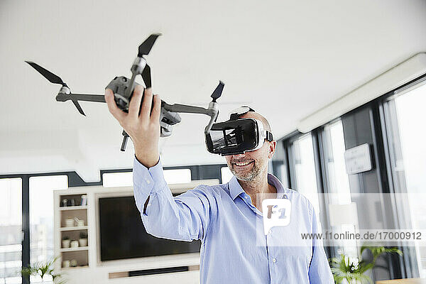 Entrepreneur wearing virtual reality headset holding quadcopter while standing at home