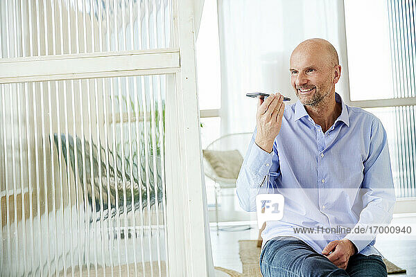 Mature businessman smiling while talking on mobile phone at home