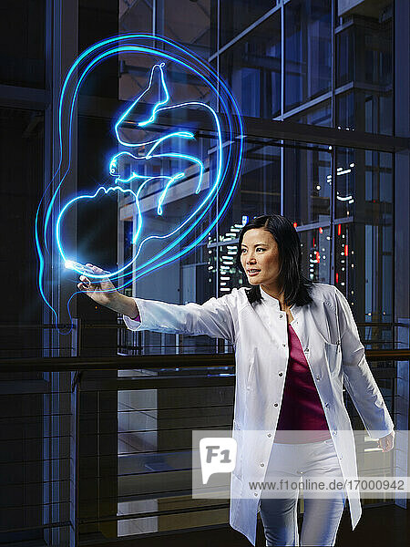 Mature female gynecologist light painting uterus with fetus at hospital
