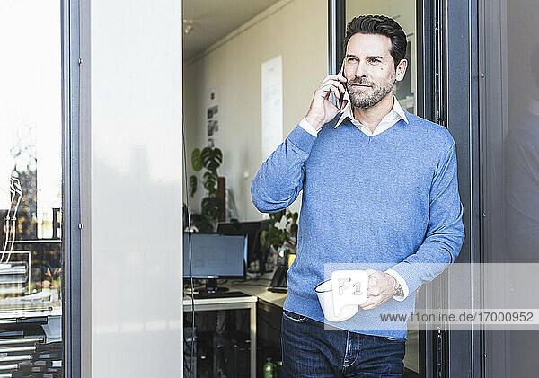 Älterer Geschäftsmann mit Kaffeetasse  der mit seinem Handy telefoniert  während er am Büroeingang steht Älterer Geschäftsmann mit Kaffeetasse, der mit seinem Handy telefoniert, während er am Büroeingang steht