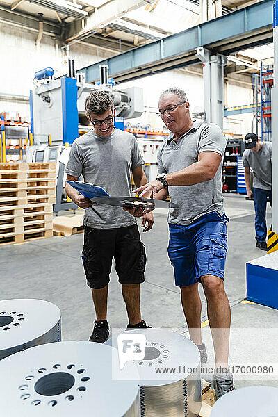 Älterer Arbeiter  der mit einem männlichen Kollegen in der Fertigungsindustrie ein Produkt untersucht