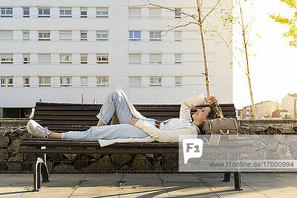 Female entrepreneur relaxing while lying down on bench