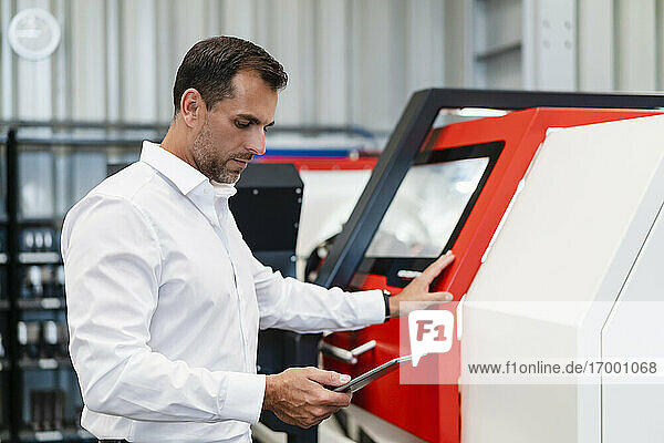 Male entrepreneur using digital tablet while standing in front of machinery at factory