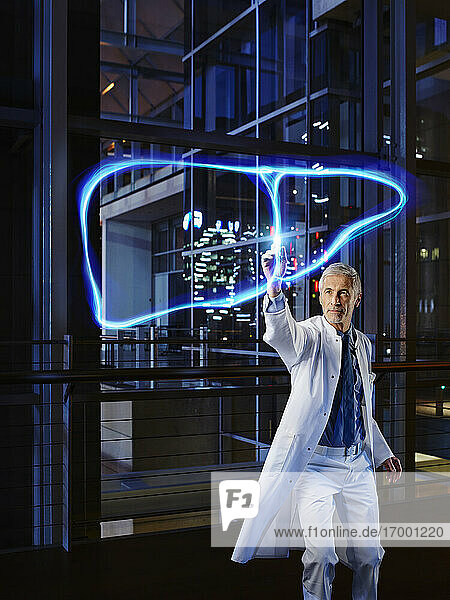 Male hepatologist light painting liver in laboratory at hospital