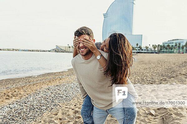 Freund nimmt ihn huckepack  während seine Freundin ihm am Strand die Augen zuhält Freund nimmt ihn huckepack, während seine Freundin ihm am Strand die Augen zuhält