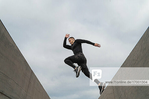 Sportsman jumping on wall against sky