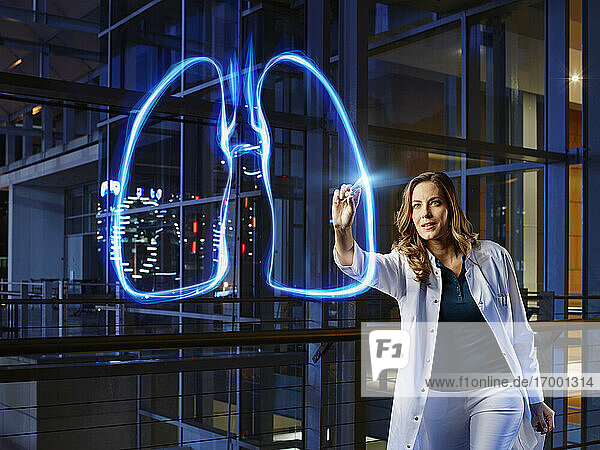 Female pulmonologist light painting lung in laboratory at hospital