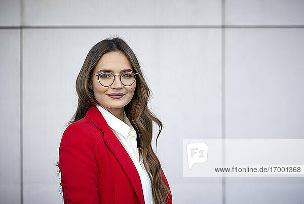Confident young businesswoman standing against wall