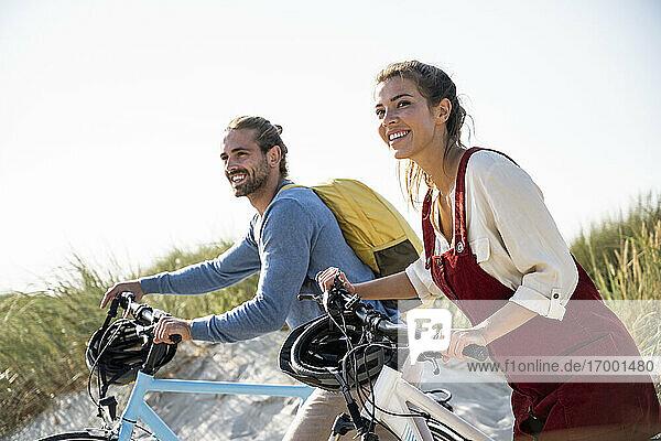 Paar mit Fahrrädern zu Fuß gegen den klaren Himmel Paar mit Fahrrädern zu Fuß gegen den klaren Himmel
