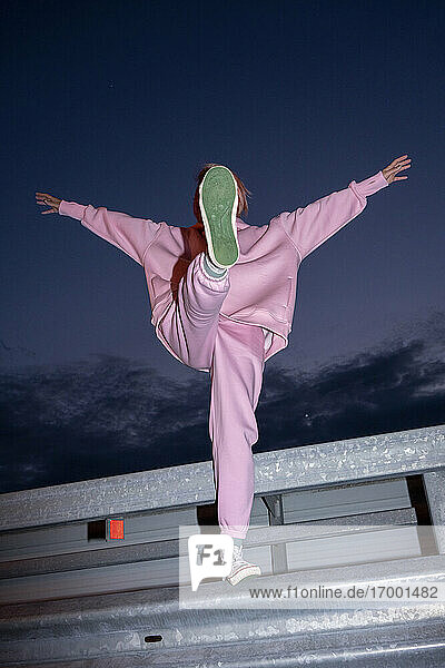 Young woman wearing pink track suit standing on one leg on road barrier at night