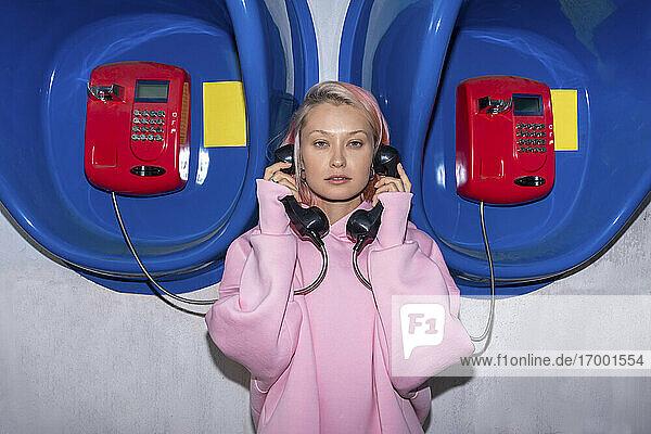 Junge Frau mit rosa Haaren und rosa Kapuzenshirt vor einer Telefonzelle stehend  mit Hörern in der Hand Junge Frau mit rosa Haaren und rosa Kapuzenshirt vor einer Telefonzelle stehend, mit Hörern in der Hand