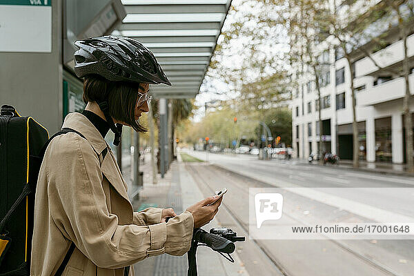 Mittlere erwachsene Frau mit Instrumentenkoffer und Elektroroller  die ein Mobiltelefon benutzt  während sie an einer Straßenbahnhaltestelle in der Stadt steht Mittlere erwachsene Frau mit Instrumentenkoffer und Elektroroller, die ein Mobiltelefon benutzt, während sie an einer Straßenbahnhaltestelle in der Stadt steht