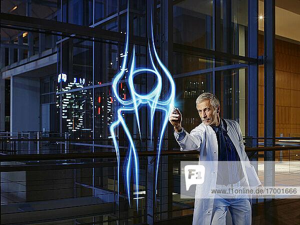 Male orthopedist light painting knee joint in laboratory at hospital