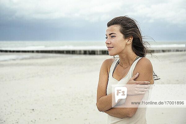 Junge Frau  die am Strand stehend die Aussicht betrachtet Junge Frau, die am Strand stehend die Aussicht betrachtet
