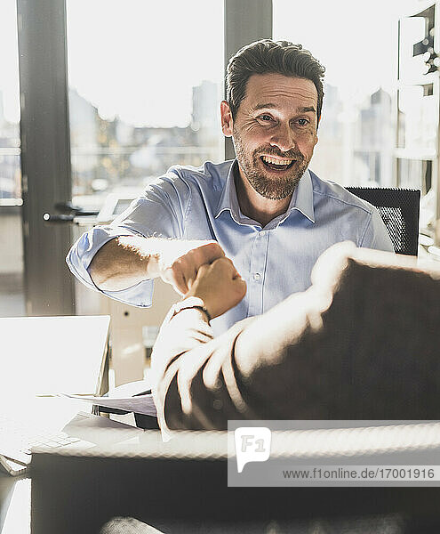 Happy businessman giving fist bump to colleague while sitting at office