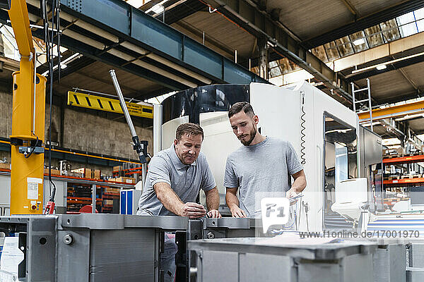 Male engineer examining product standing by young coworker in industry