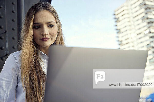Young businesswoman using laptop while sitting outdoors