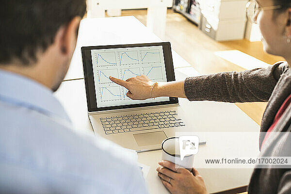 Businesswoman with coffee cup explaining diagram on laptop to businessman while sitting at office