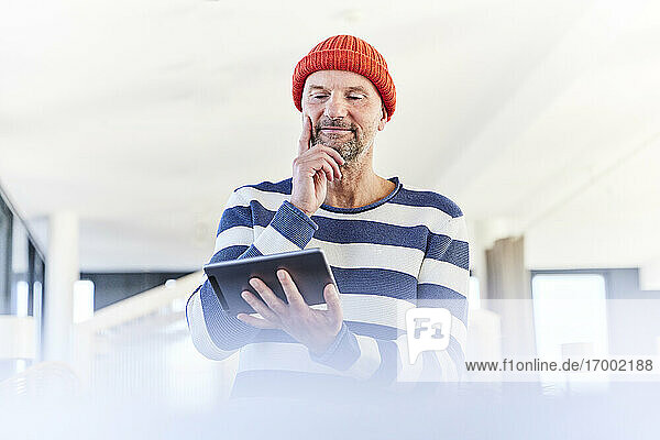 Thoughtful man using digital tablet while standing at home