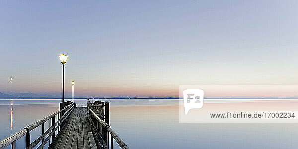 Germany  Bavaria  Clear sky over wooden pier on shore ofChiemsee lake at dusk