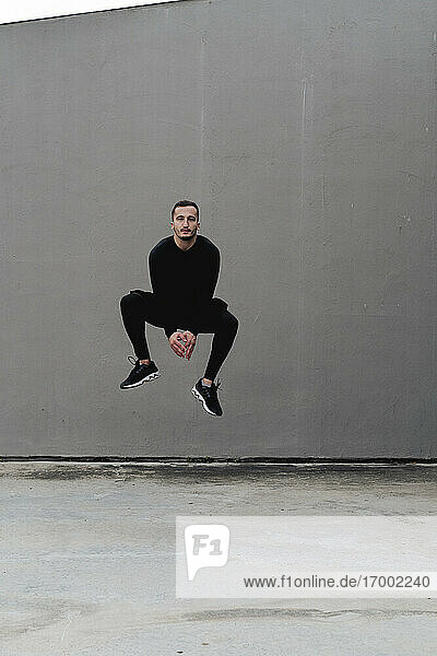 Young man jumping against wall