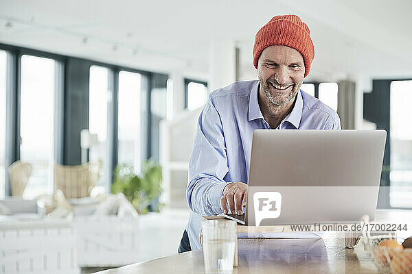 Businessman wearing knit hat working on laptop while sitting at home