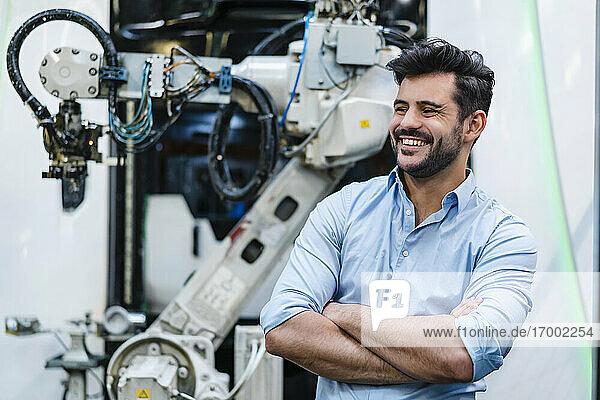 Lächelnder männlicher Unternehmer mit verschränkten Armen  der wegschaut  während er neben einem Roboterarm in der Industrie steht