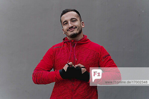 Smiling man with hand covered in boxing wrap standing against wall
