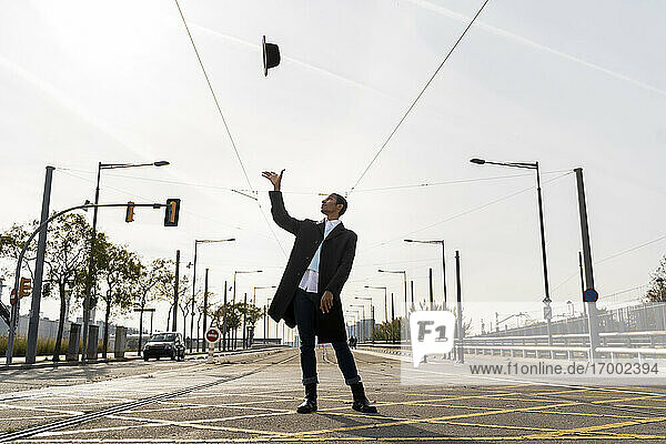 Young man throwing his hat in air on street during sunny day