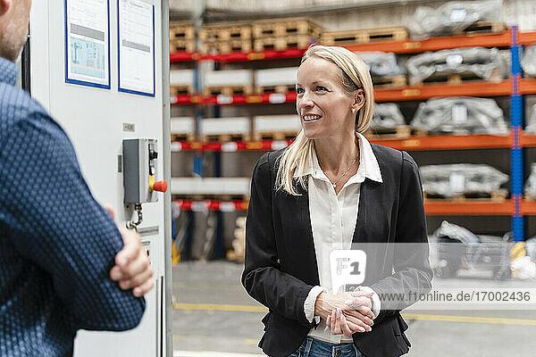 Lächelnde Geschäftsfrau mit verschränkten Händen  die mit einem männlichen Kollegen in einer Fabrik diskutiert