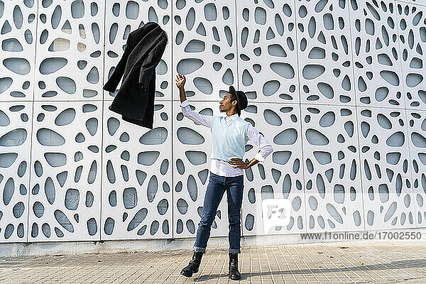 Young man standing on one leg while throwing jacket in air against pattern wall