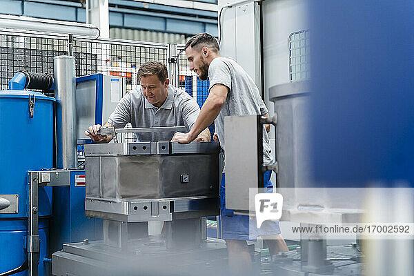 Ältere männliche Arbeiter  die eine Maschine in einer beleuchteten Fabrik messen