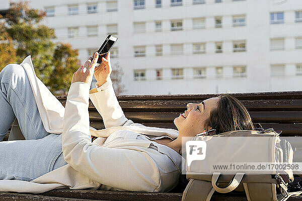 Smiling businesswoman using smart phone while lying down on bench