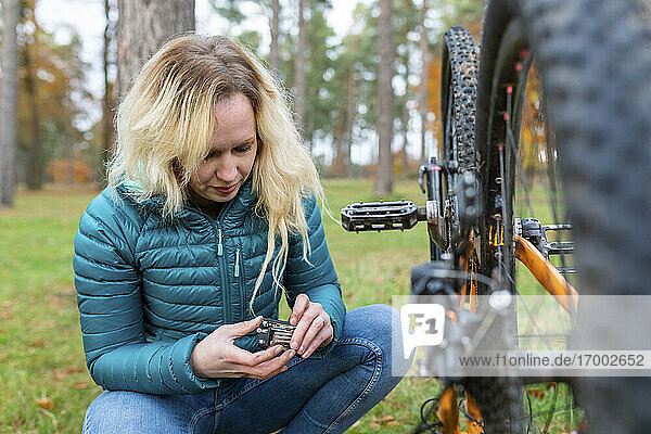 Woman with blond hair repairing bicycle at Cannock Chase
