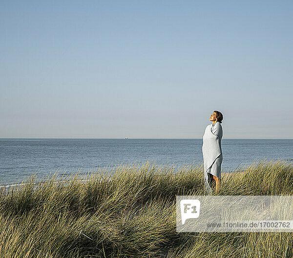 Junge Frau in Schal gehüllt vor klarem Himmel stehend Junge Frau in Schal gehüllt vor klarem Himmel stehend