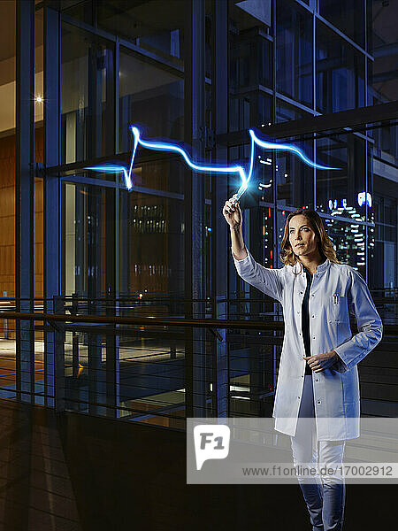 Female cardiologist light painting heart attack in laboratory