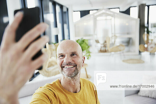 Man taking selfie through smart phone while standing at home