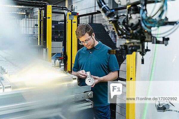 Male factory worker examining machine part while standing at industry