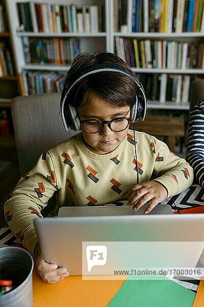 Junge benutzt Laptop für Hausunterricht am Tisch Junge benutzt Laptop für Hausunterricht am Tisch