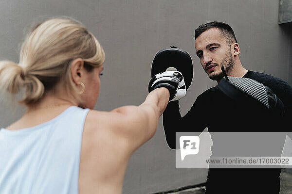 Sportswoman sparring with man while standing against wall