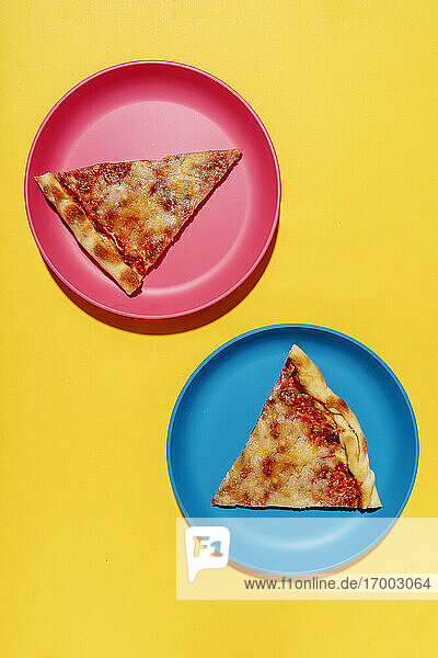 Two slices of pizzaMargheritaon blue and pink plates against yellow background