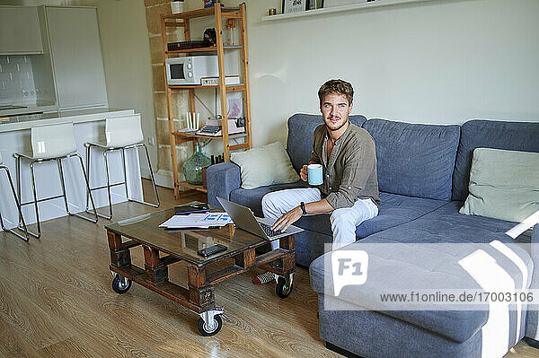 Male entrepreneur holding coffee mug looking away while sitting on sofa in living room
