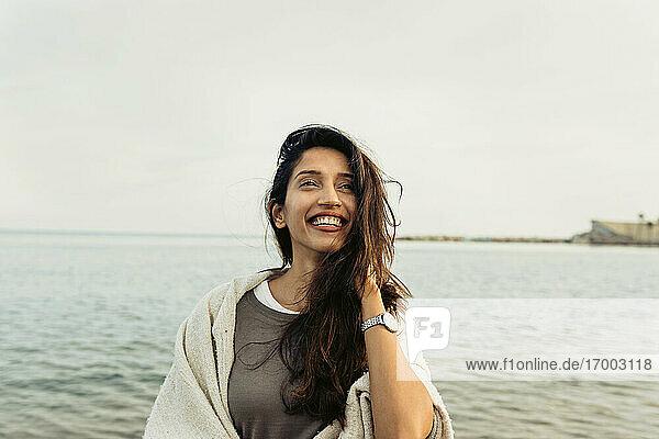 Lächelnde Frau mit Hand im Haar  die gegen den klaren Himmel am Strand wegschaut Lächelnde Frau mit Hand im Haar, die gegen den klaren Himmel am Strand wegschaut