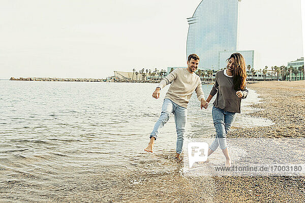 Happy young couple having fun while walking at beach against clear sky