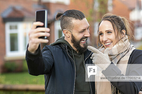 Young woman gesturing while taking selfie with cheerful boyfriend outside new house