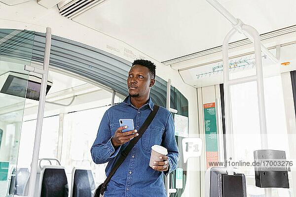 Geschäftsmann schaut mit Smartphone und wiederverwendbarem Kaffeebecher im stehenden Zug weg Geschäftsmann schaut mit Smartphone und wiederverwendbarem Kaffeebecher im stehenden Zug weg
